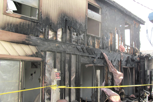 The charred remains of a 2-story home are seen after a fire ravaged the house Thursday. (Staff photo by Lela Weber)