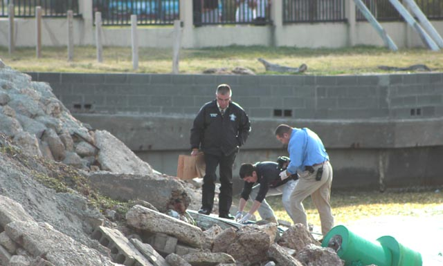 Law enforcement authorities are seen taking photographs and observing the area where Ray Roman Marchan's body was believed to be retrieved on Thursday. (Staff photo by Craig Alaniz)