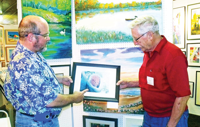Greg Johnson points out a feature of his underwater photography to Tom Leeman. (Courtesy photo)