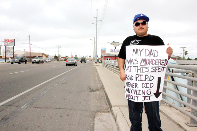 Andres Bridges is seen on Queen Isabella Blvd. in Port Isabel with a sign raising awareness about his father's death. (Staff photo   by Ray Quiroga)
