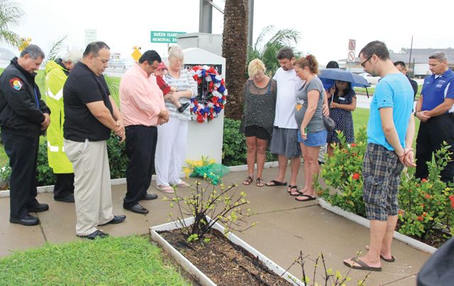 (Staff photo by Ray Quiroga) Local officials, family and friends of the Sept. 15, 2001 causeway collapse victims are seen Monday at a memorial site in Port Isabel observing a moment of silence for the tragedy's 13th anniversary.