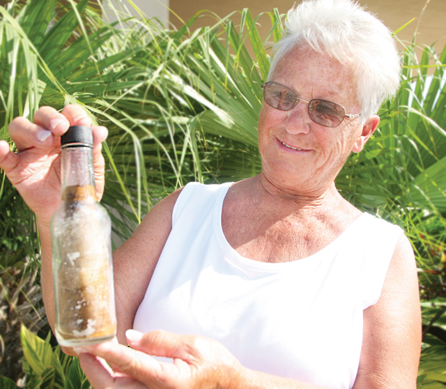 (Staff photo by Estevan Medrano) Carole Mahalak shows off the most recent addition to her message in a bottle collection.