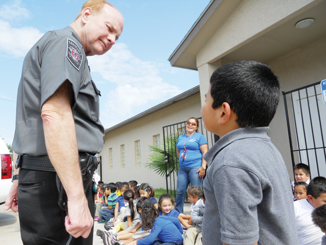 (Staff photo by Estevan Medrano) Reserve Deputy Don Duncan of the Cameron County Constable's Office, Precinct 1, answers a question from a child at the Esperanza B. Garza Canter.