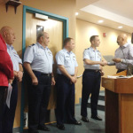 SPI Mayor Barry Patel presents Lt. Cmdr. William Bell with a proclamation welcoming him, on behalf of the City, as the new SPI Coast Guard Station commander.