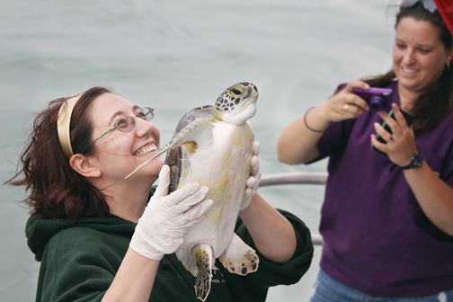 "Debra Cadena smiles as she holds ""Clifford"" up for onlookers to see before releasing him back into the bay. (Staff photo by Dina Arevalo)"