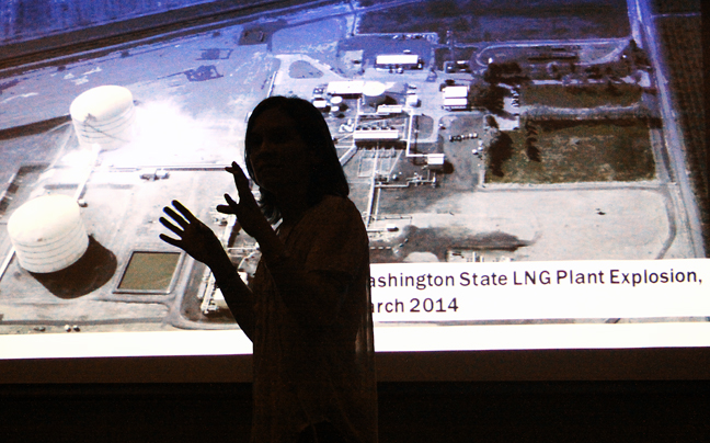 An image of the aftermath of an explosion at an LNG facility is shown on a projection screen as Sierra Club member Stefanie Herwick lists concerns with several such plants that may be built in the Laguna Madre region. (Staff photo by Dina Arevalo).
