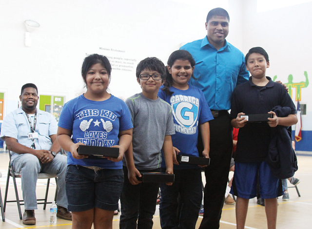 Joe Vega stands with four members of the Boys & Girls Club of the Laguna Madre shortly after surprising them with tablet computers. (Staff photo by Dina Arevalo).