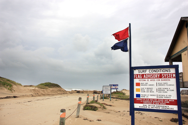 Red and blue flags warn beachgoers of unsafe conditions, including high tides, strong risks of rip currents, and the presence of harmful sea life in the form of red tide. (Dina Arévalo |Staff photographer)